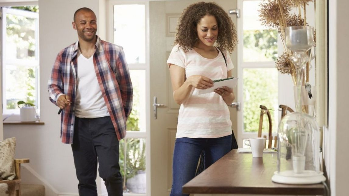 Couple looking at post after walking through front door