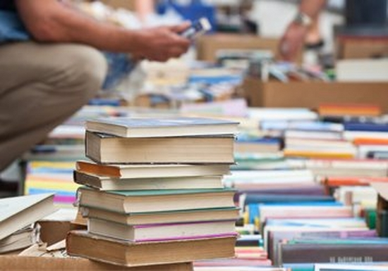 Stacked up books being sold outdoors in a market