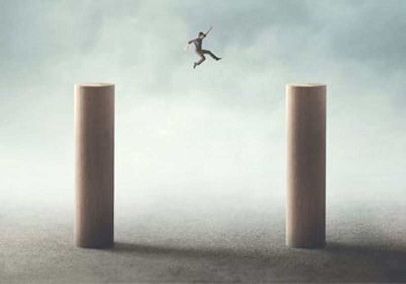 A man leaps from one pillar to another.