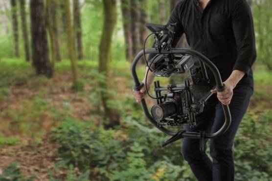 A man holding an EOS C500 Mark II on a gimbal, filming in a forest.
