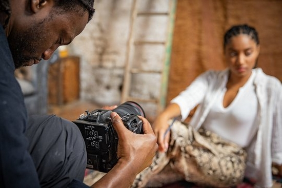 Jolade Olusanya holds a Canon EOS C70 camera to film a woman seated on the floor in front of him.
