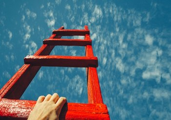 A hand reaching onto a red ladder, which points at a bright blue sky
