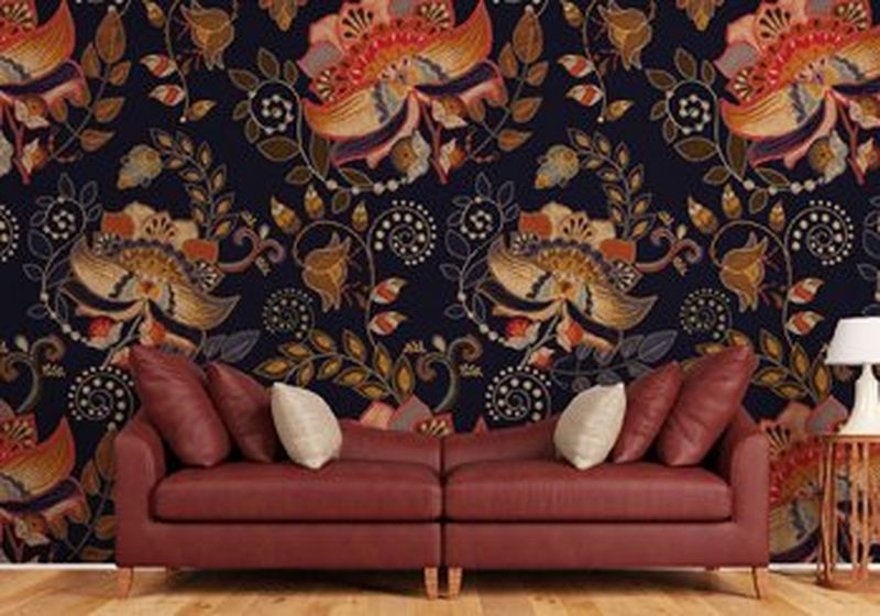 A brown leather sofa and cushions with an occasional table and a lamp to the right. Behind is wallpaper in a repeating design of orange, black and brown leaves and flowers in a modern brocade style, often seen in furnishings and wall coverings.