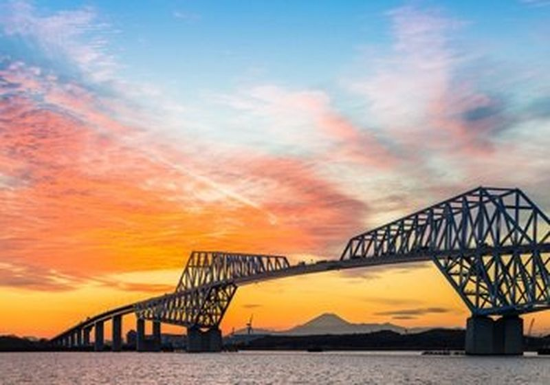 A panorama of the Tokyo Gate Bridge under a beautiful orange sunset