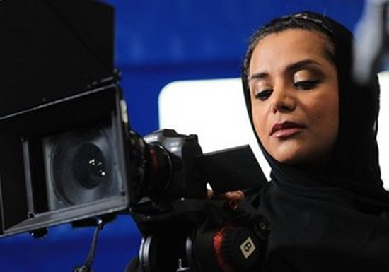 Filmmaker & Associate Producer, Nayla Al Khaja. She holds a film camera and stands against a blue background.