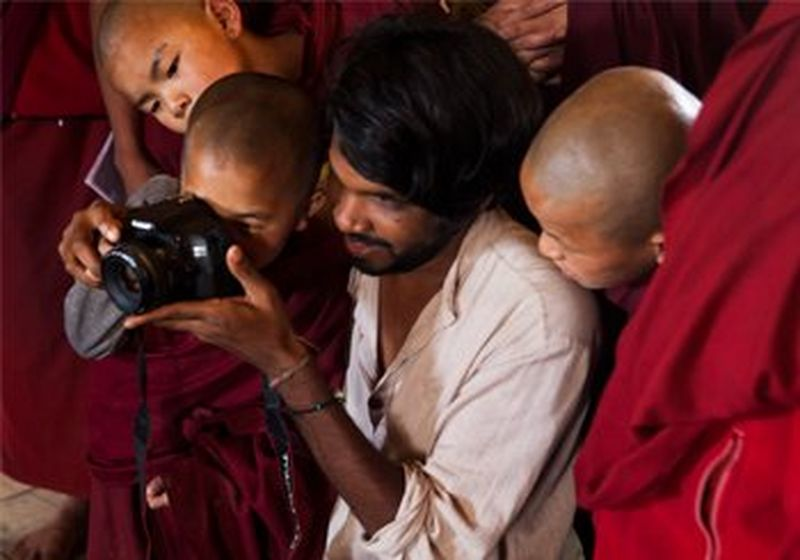 Jérôme Gence shows a group of young monks how to use his DSLR camera to take ID photos for their passports.