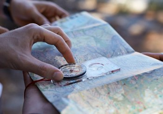 Hands, holding a compass over a map