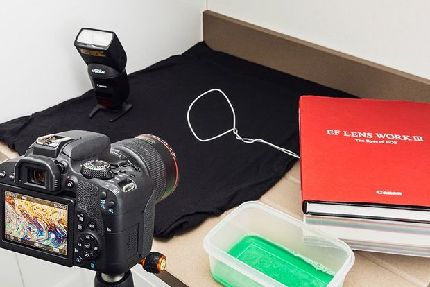 A camera set up to photograph a desk with books on the top.