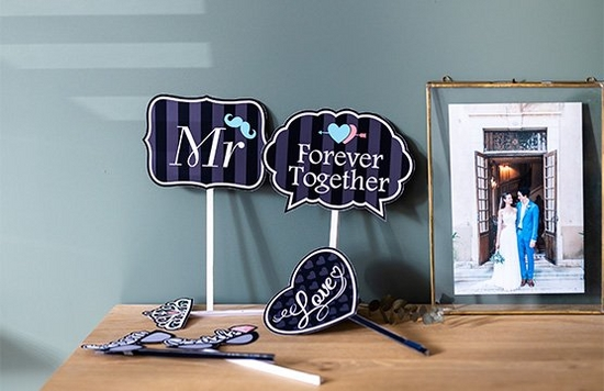 Printed decorations and hand-held signs for a wedding day next to a portrait of a bride and groom in a frame.