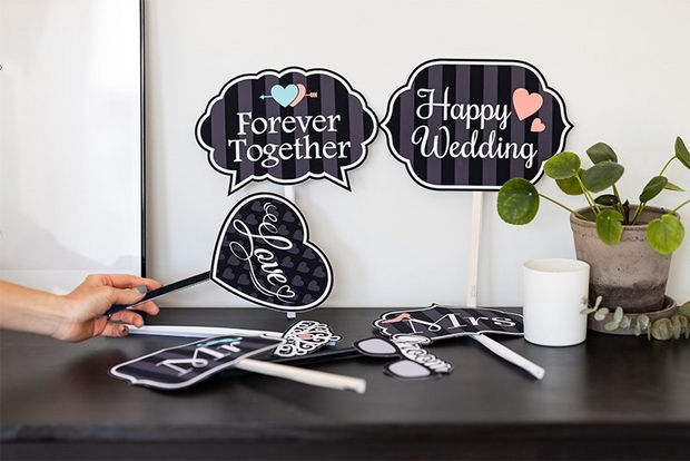 Printed decorations and hand-held signs for a wedding day.