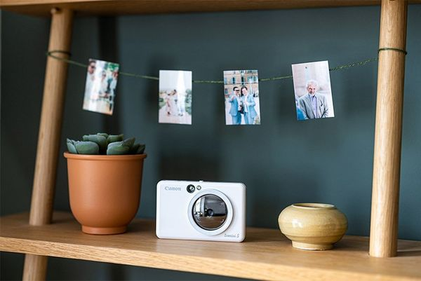 A selection of images displayed on a string above a bookshelf holding a Canon Zoemini S.