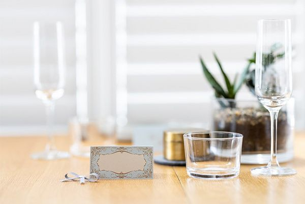A tabletop with champagne flutes and home-printed place-cards.