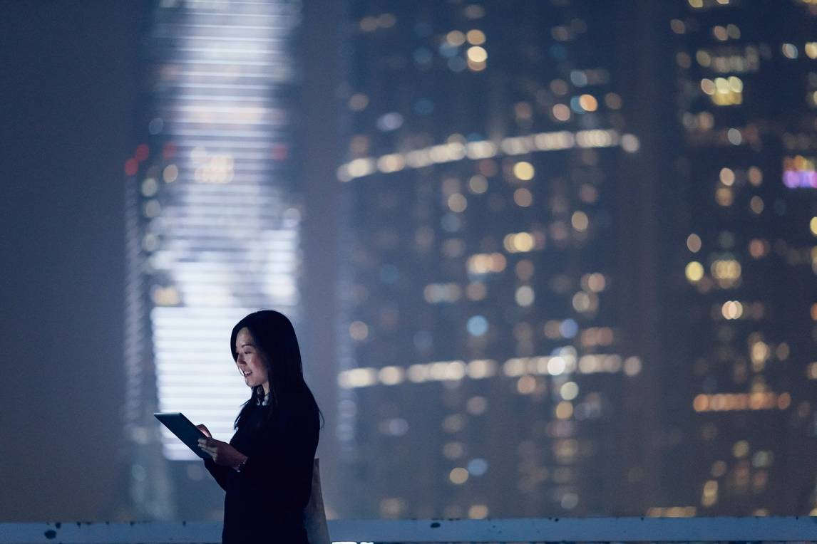 Woman on tablet at night in front of blurred building and lights