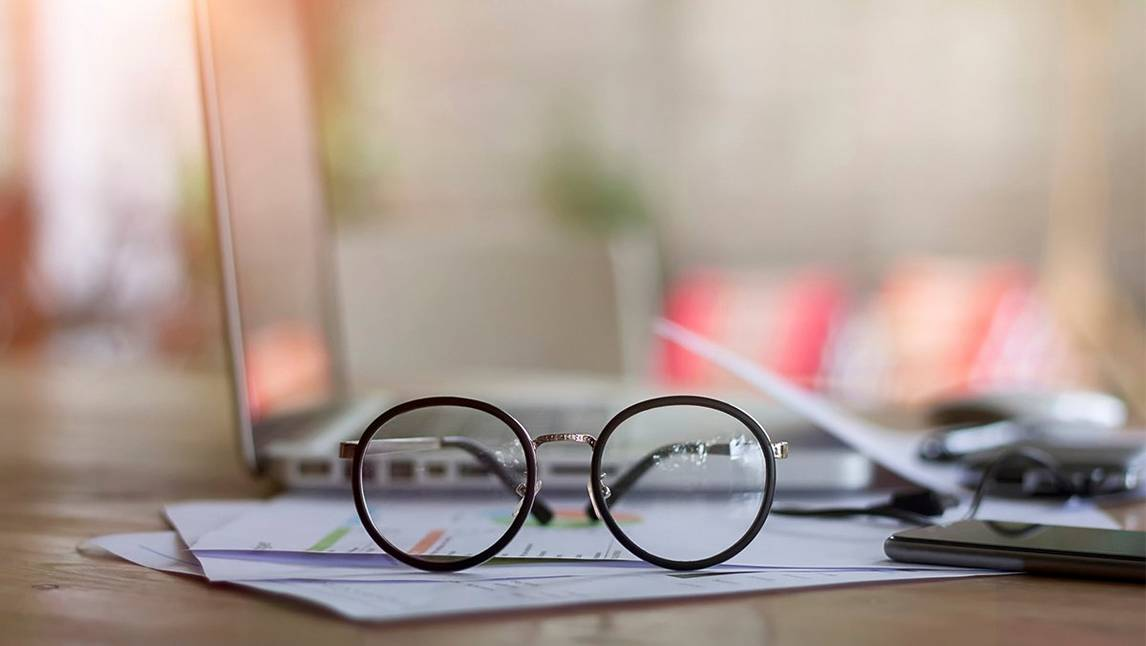Glasses resting on documents on desk