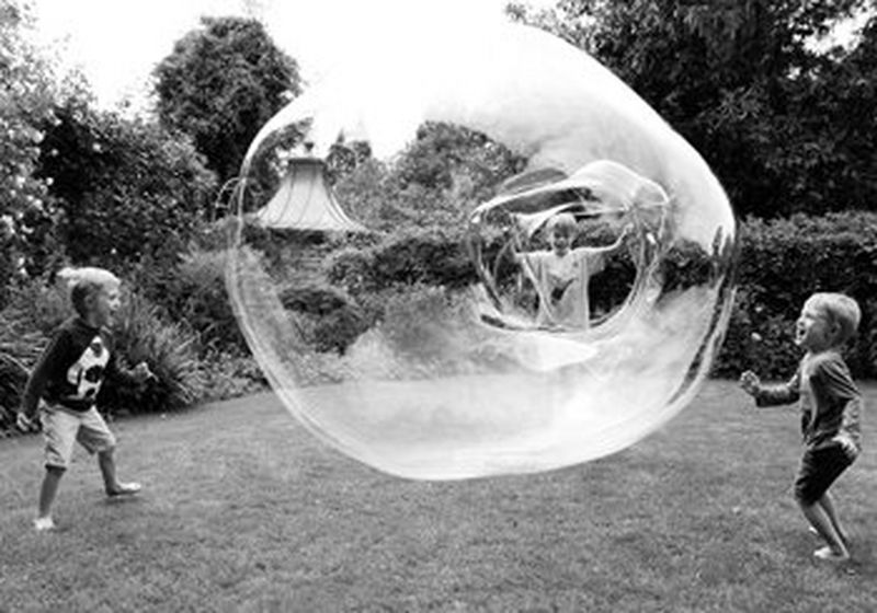 Three children in a garden, one is making a huge soap bubble from a hoop. The others are laughing and screaming with the fun of it all.