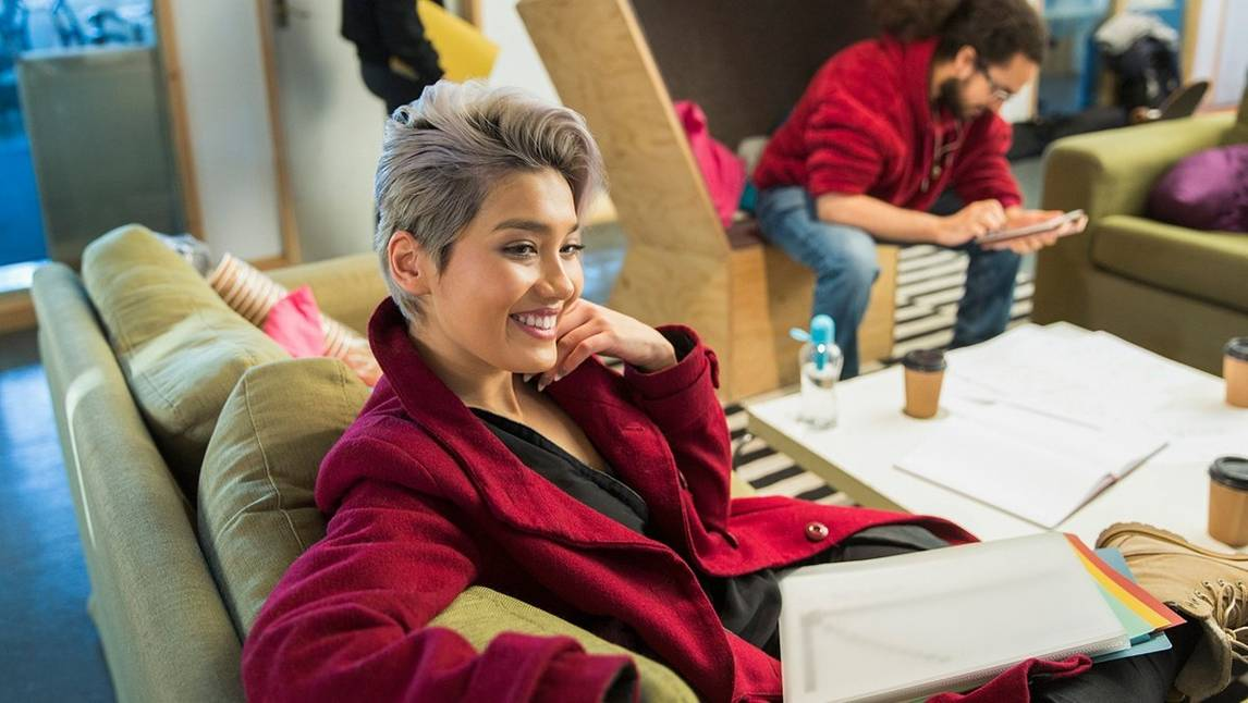 Short-haired woman in red jacket smiles from sofa