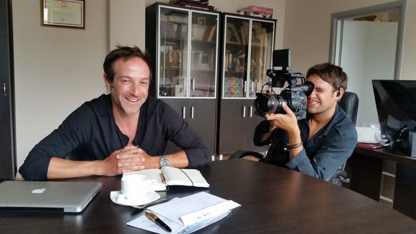 DOP Jake Swantko pointing a videocamera at Bryan Fogel while both sit at a table.