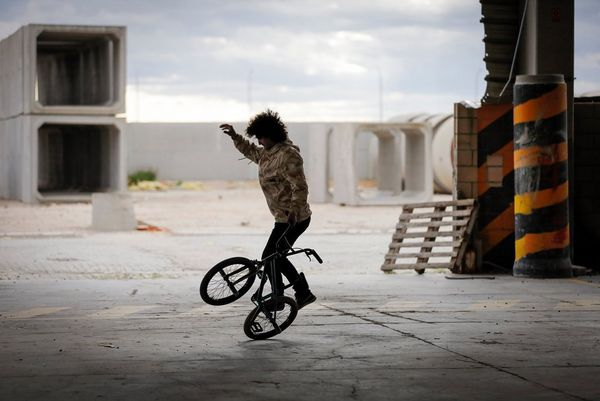 A man in an empty industrial space balances on the back wheel of the BMX he is riding.
