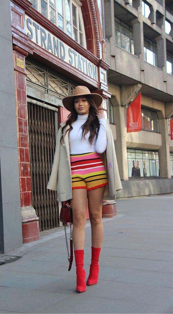 A model wearing striped shorts and red boots, standing outside Strand Station