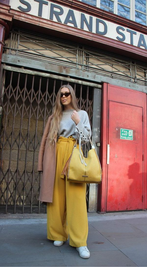A model, wearing yellow trousers and carrying a matching handbag, standing outside Strand Station