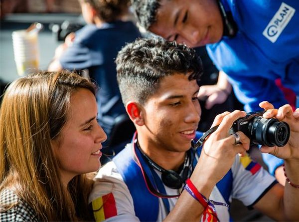 A young woman and two young men look at the display on the back of a Canon camera. © Plan International | Greetje Van Buggenhout