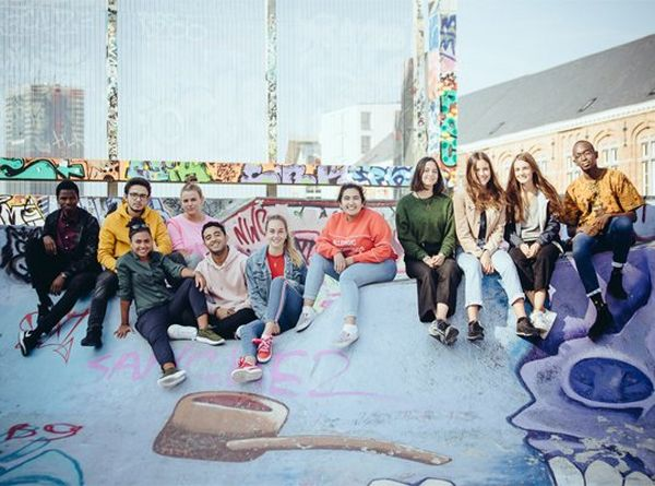 A group of eleven smiling young people, wearing jeans and sweaters, sit at a skate park, posing for the camera.