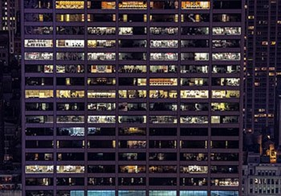 A building, photographed from the outside at night, showing dozens of lit offices.
