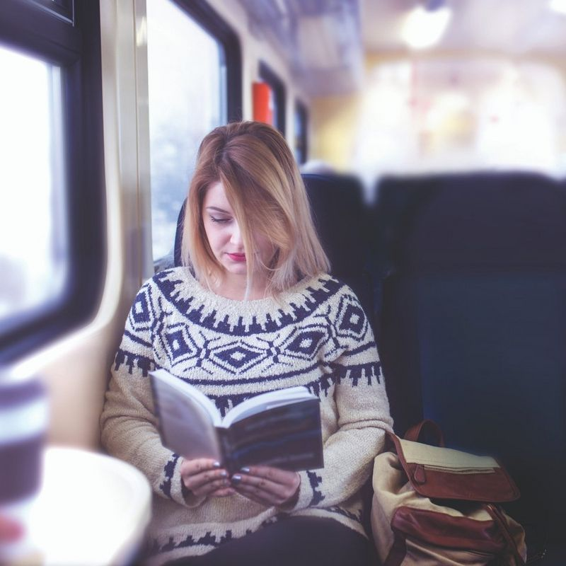 Girl reading book on train