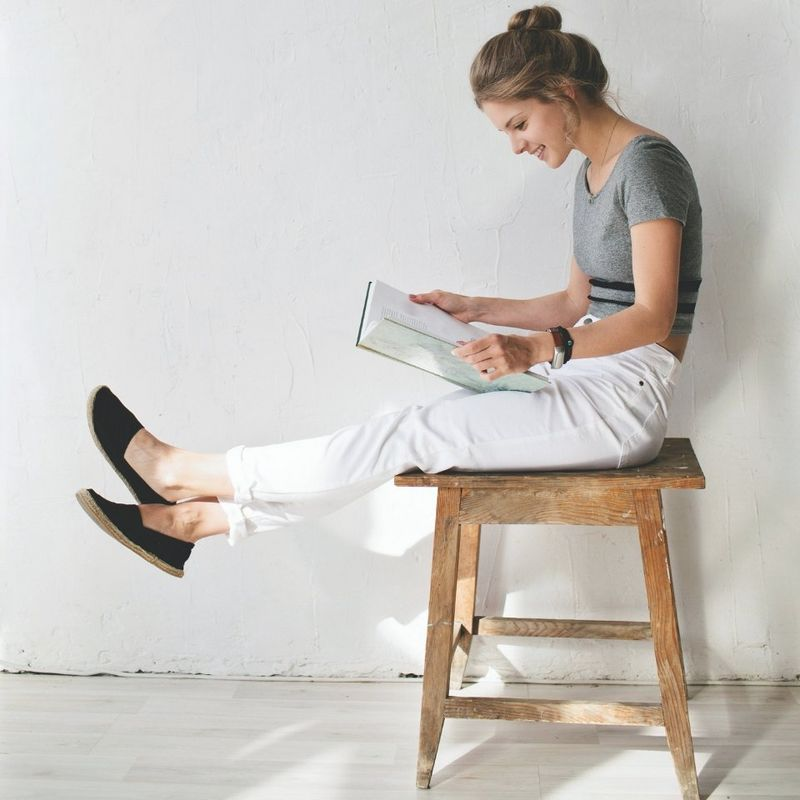 Girl sat on stool reading book