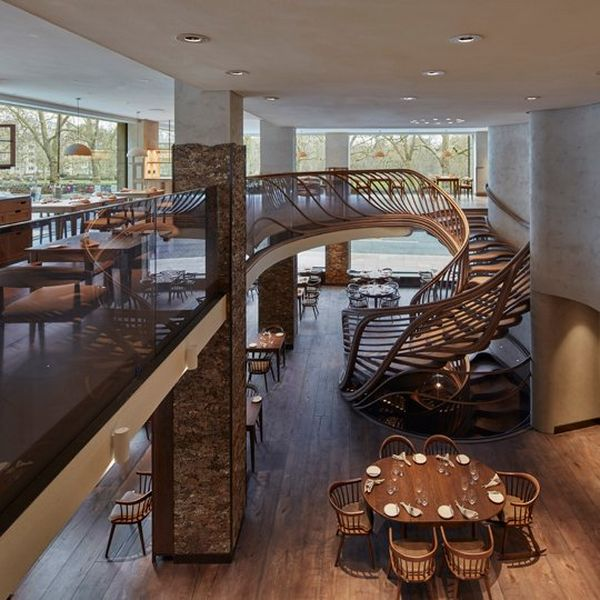 A wide view of the restaurant, showing the winding oak staircase against the floor to ceiling windows that overlook Green Park.