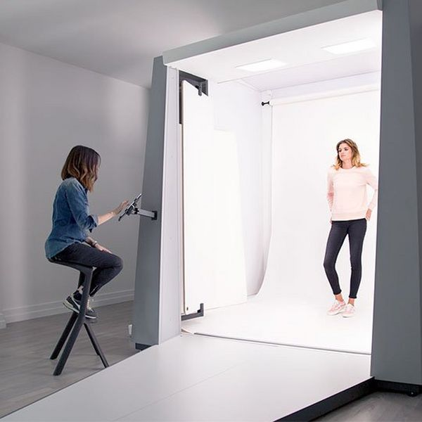 A model stands in a Styleshoots booth, as a stylist controls the shot with an Apple iPad.