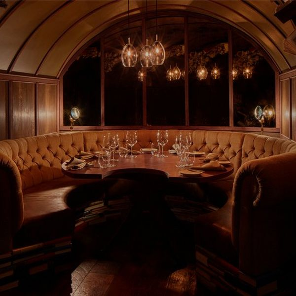 A small, dimly lit, private dining room with seating in a semi-circular booth ad wood panelled walls.