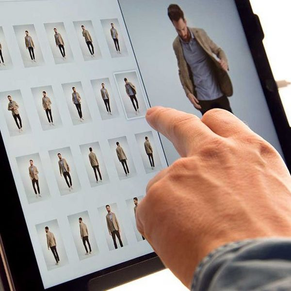 A man's hand selects an image on an Apple iPad.