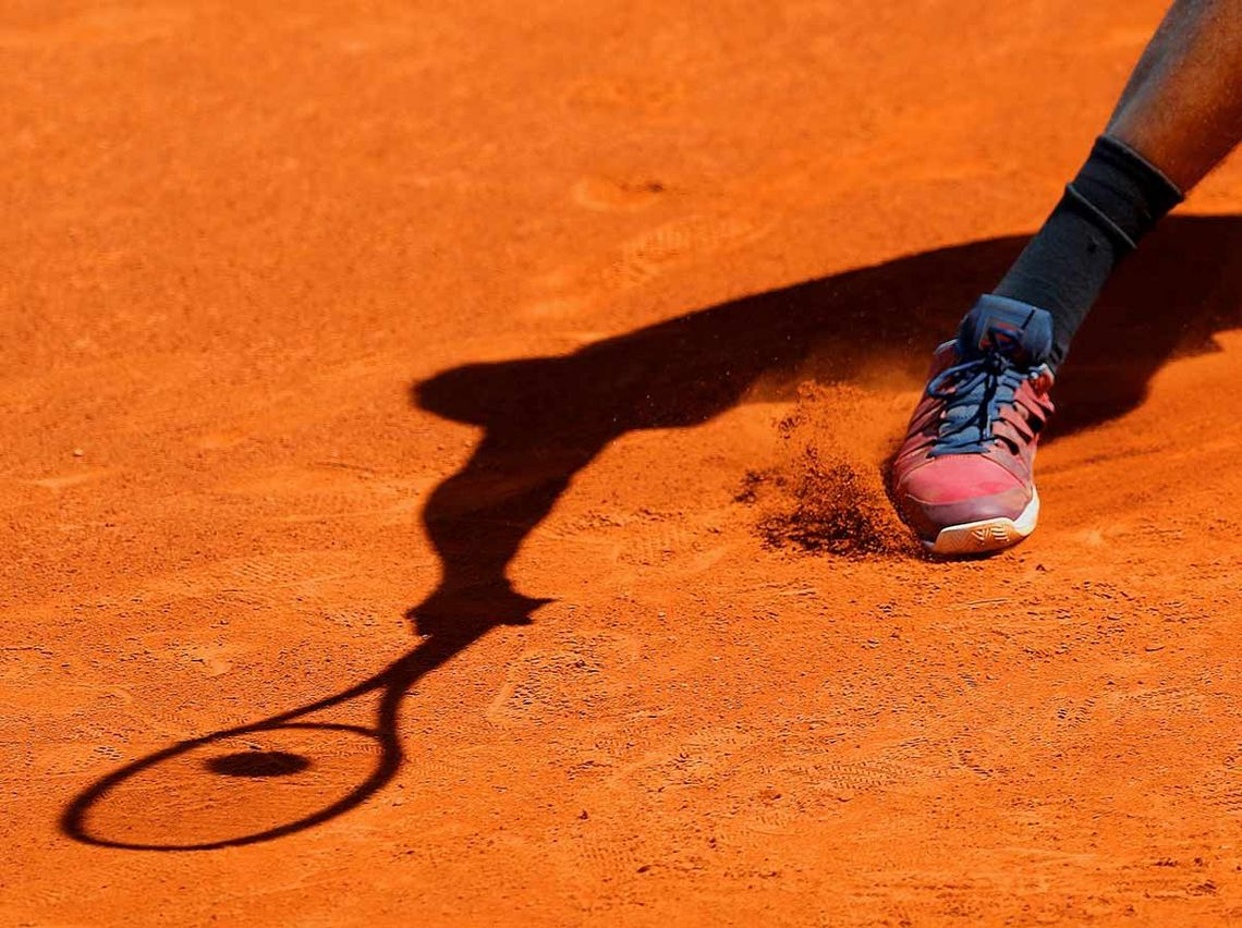 A close up shows tennis star Nick Kyrgios's right foot skidding on a clay court, while shadow captures how his racket hit the ball. © Marc Aspland