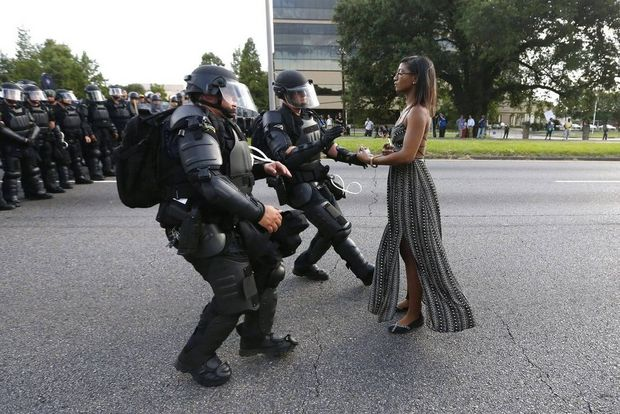 Taken on a Canon EOS-1D X showing protester Iesha Evans confronting police over African American civil rights police brutality.