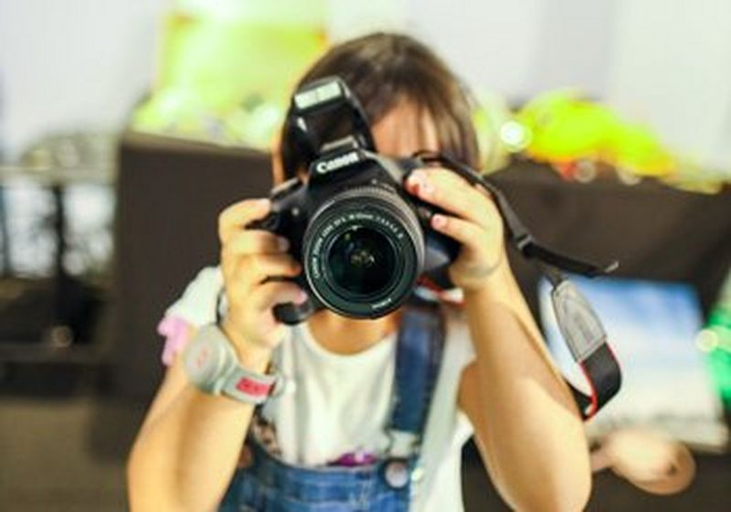 A child holds a Canon camera, obscuring his/her face