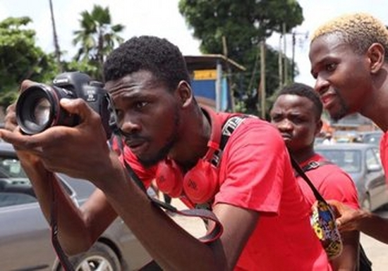 Four young men, one holding a camera, look carefully at the shot they are about to take.