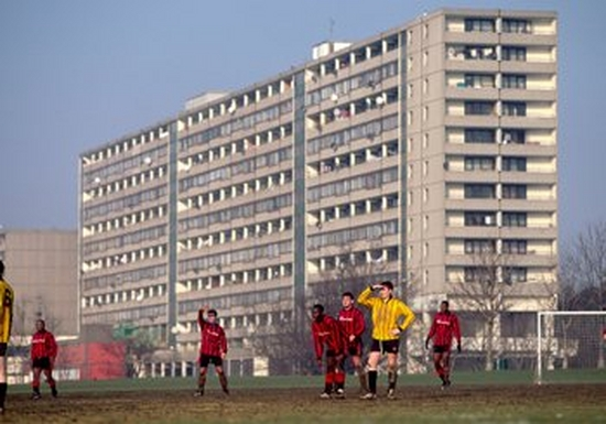 A Sunday league football match being plated on an amateur muddy pitch by players in red or yellow shirts. In the immediate background looms a huge, concrete block of flats.
