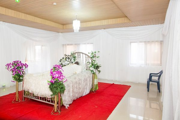 In Ghana, the body of a woman is laid out respectfully on a white bed in a white-draped room with a red rug.
