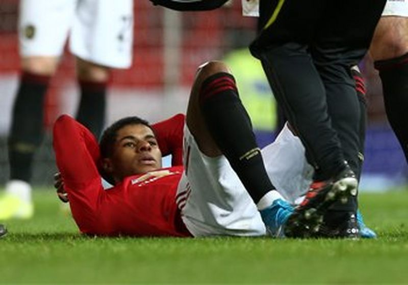 A Man Utd player lies on his back on the pitch, awaiting treatment. (Photo courtesy of Manchester United FC.)