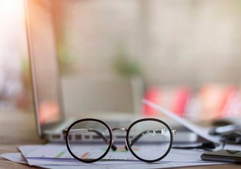 A pair of spectacles sat on top of paperwork, in front of a laptop and next to a phone