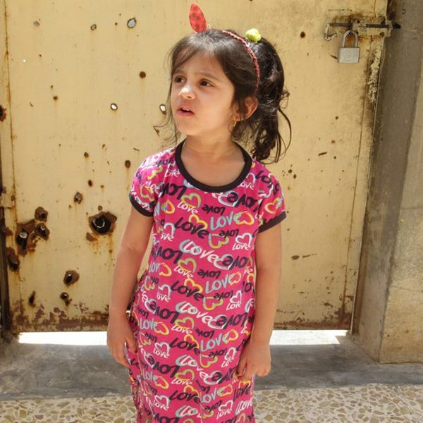 A little girl, wearing a dress with the word 'love' printed on it in a repeating pattern, stands in front of a bullet-hole riddled door.