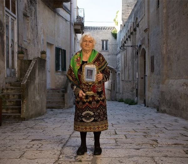 An older, shawled woman stands on a cobbled street, holding a photograph in a frame.