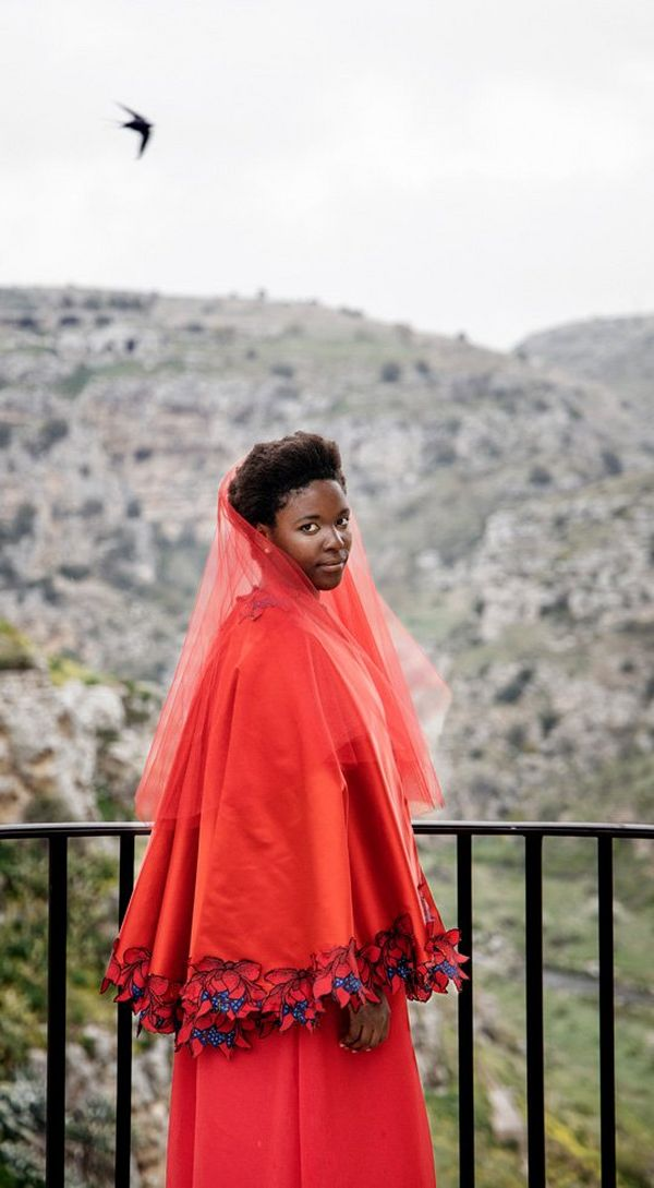 A woman in a red dress, shawl and veil, stands by railings, overlooking mountains.