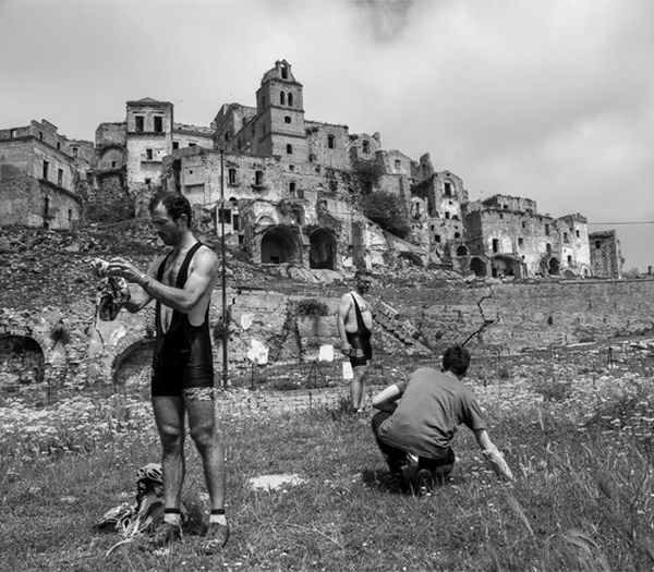 A black and white image of three men in lycra, standing in front of the buildings of Sassi di Matera.