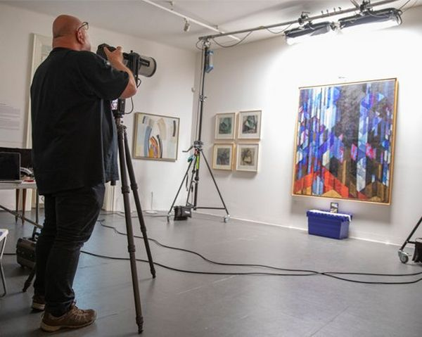 A man photographs a painting
