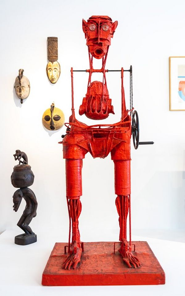 A red wire sculpture standing on a red base, which resembles a human by Karel Nepraš