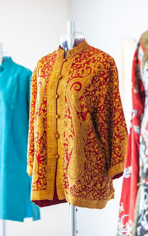 A gold jacket with red brocade and a mandarin collar displayed on a mannequin.