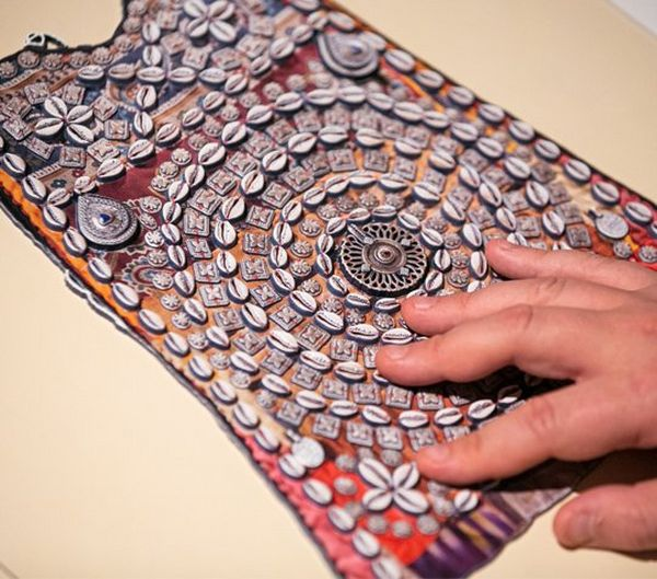 A hand touches a reproduction of a piece of indigenous artwork.