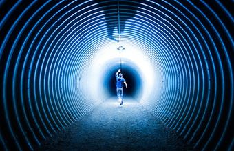 Man running down a tunnel towards a black hole